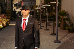 Man in suit standing in a business area. A young man in a suit with a red tie and hat standing in a business park Royalty Free Stock Photos