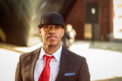 Man in suit standing in a business park. A young man in a suit with a red tie and hat standing in a business park Stock Images