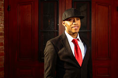Man in suit in standing in doorway. A young man in a suit with a red tie and hat standing in front of wood doors Royalty Free Stock Photography