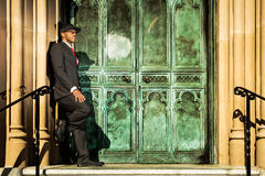 Man in suit standing in front of old doors. A young man in a suit with a red tie and hat standing against old building Stock Photos