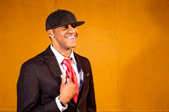 Man in suit standing in front of yellow wood wall smiling. A young man in a suit with a red tie and hat standing in a business park Stock Images
