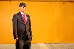 Man in suit standing in front of yellow wood wall. A young man in a suit with a red tie and hat standing in a business park Stock Photo