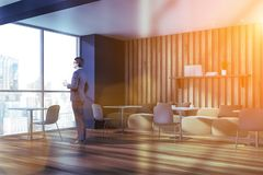 Man in gray and wooden cafe interior. Man in suit standing in modern cafe interior with gray and wooden walls, beige sofas and white chairs and square tables royalty free stock photo