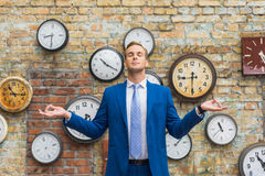 Man in suit standing near wall with clocks Royalty Free Stock Images