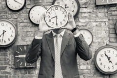 Man in suit standing near wall with clocks Royalty Free Stock Photo
