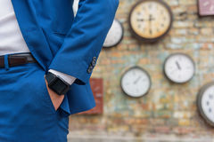 Man in suit standing near wall with clocks stock image