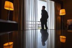Man in suit standing near window Stock Photo