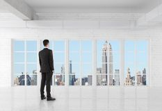 Man in suit standing in room. And looking at window Stock Photo