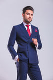 Man in suit standing in studio posing with hand in pocket Stock Photo