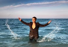 Man in suit stands in sea and splash water Stock Images