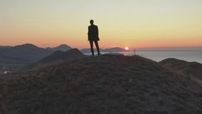 A man in a suit stands on top of a hill and looks at the dawn over the sea