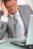 Man in suit staring at laptop. Perplexed man in suit staring at laptop computer Stock Photo