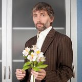 Man in suit stretches bouquet of flowers. Man in business suit stretches bouquet of flowers Stock Images