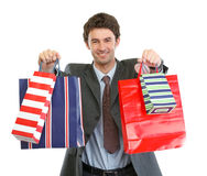 Man in suit stretching hand with shopping bags Royalty Free Stock Images