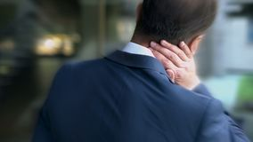 Man in suit suffers from neck pain, passive lifestyle causes spinal problem royalty free stock photos