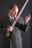 Man in a suit with a sword motioning 'come here' Stock Images