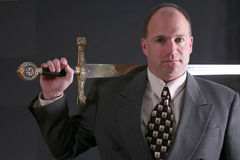 Man in a suit with sword slung over shoulder