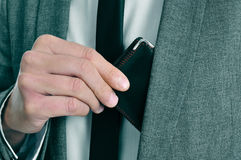 Man in suit taking out his wallet. Man wearing a suit taking out his wallet from his jacket royalty free stock photo