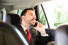 Man in a suit talking on the phone Stock Images