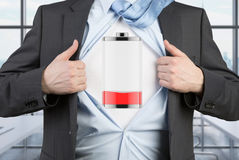 A man in a suit is tearing the blue shirt. Low level of power on the chest. Royalty Free Stock Photography