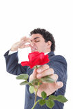 Man in suit throws a rose and gives it to the camera  with face Stock Images