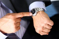 Man in suit and tie check out time at silver wristwatch Royalty Free Stock Images