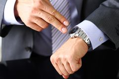 Man in suit and tie check out time at silver wristwatch Stock Photography