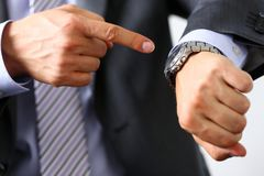Man in suit and tie check out time at silver wristwatch. Closeup. Show and point with finger, waste minute, modern punctual life style, start hurry, job idea Royalty Free Stock Image