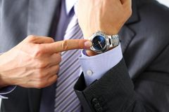 Man in suit and tie check out time at silver wristwatch. Closeup. Show and point with finger, waste minute, modern punctual life style, start hurry, job idea Royalty Free Stock Photography