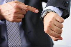Man in suit and tie check out time. At silver wristwatch closeup. Show and point with finger waste minute modern punctual life style start hurry job idea last Stock Photo