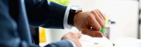 Man in suit and tie check out time at silver wristwatch. Closeup. Show and point with finger waste minute modern punctual life style start hurry job idea last Royalty Free Stock Image