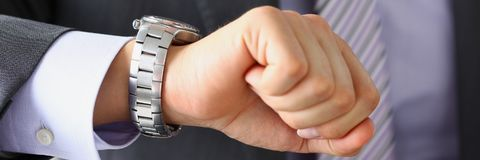 Man in suit and tie check out time at. Silver wristwatch closeup. Waste minute modern punctual life style start hurry job idea last second clockwork precision Royalty Free Stock Photo