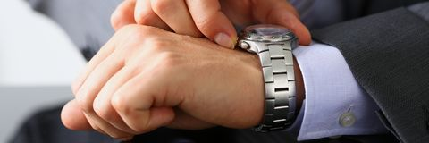 Man in suit and tie check out time at. Silver wristwatch closeup. Waste minute modern punctual life style start hurry job idea last second clockwork precision Stock Photography