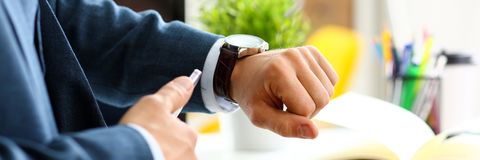 Man in suit and tie check out time at silver wristwatch. Closeup. Show and point with finger waste minute modern punctual life style start hurry job idea last Royalty Free Stock Photography