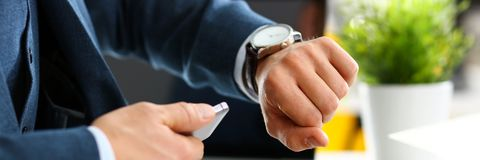 Man in suit and tie check out time at silver wristwatch. Closeup. Show and point with finger waste minute modern punctual life style start hurry job idea last Stock Photos