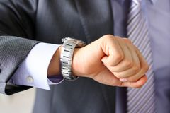 Man in suit and tie check out time at silver wristwatch. Closeup. Waste minute, modern punctual life style, start hurry, job idea, last second, clockwork Royalty Free Stock Photos
