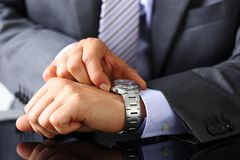 Man in suit and tie check out time at silver wristwatch. Closeup. Waste minute, modern punctual life style, start hurry, job idea, last second, clockwork Royalty Free Stock Images