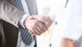 Man in suit and tie give hand as hello in office stock image