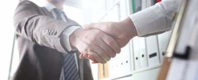 Man in suit and tie give hand as hello in office stock photos