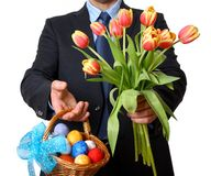 Man in suit and tie gives tulips and Easter basket Royalty Free Stock Image