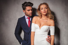 Man in suit and tie looks at his blonde woman. Young handsome elegant men in suit and tie looks at his blonde women in white dress, she is looking at the camera Stock Photography