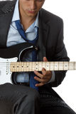 Man in suit and tie playing electric guitar Royalty Free Stock Photography