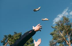 Man throwing his shoes up catches his hands sky background royalty free stock photography
