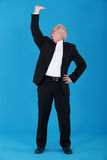 Man in suit touching ceiling Royalty Free Stock Photos