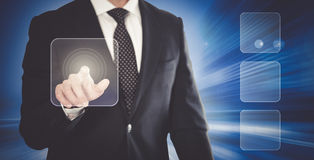 Man in suit touching screen. On the background of modern glass buildings Royalty Free Stock Photography