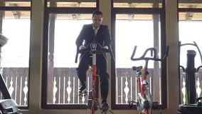 Man with suit training at static bicycle at gym, break at work. UHD 4K stock video