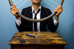 Man in suit trying to fix a bicycle tyre Stock Images