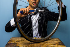 Man in suit trying to fix a bicycle tyre Stock Photo
