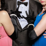 Man in suit and two elegant women in dresses. Royalty Free Stock Photo