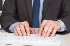 Man in suit is typing at the keyboard Royalty Free Stock Images